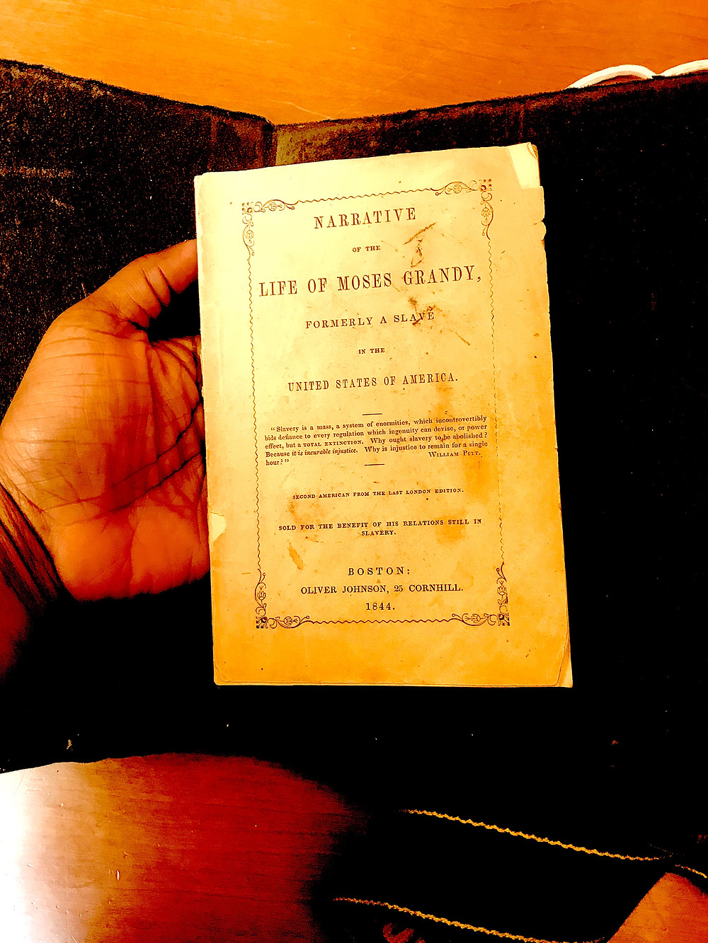 Holding the 1844 edition of Moses Grandy's narrative of enslavement. Albert and Shirley Small Special Collections, University of Virginia.