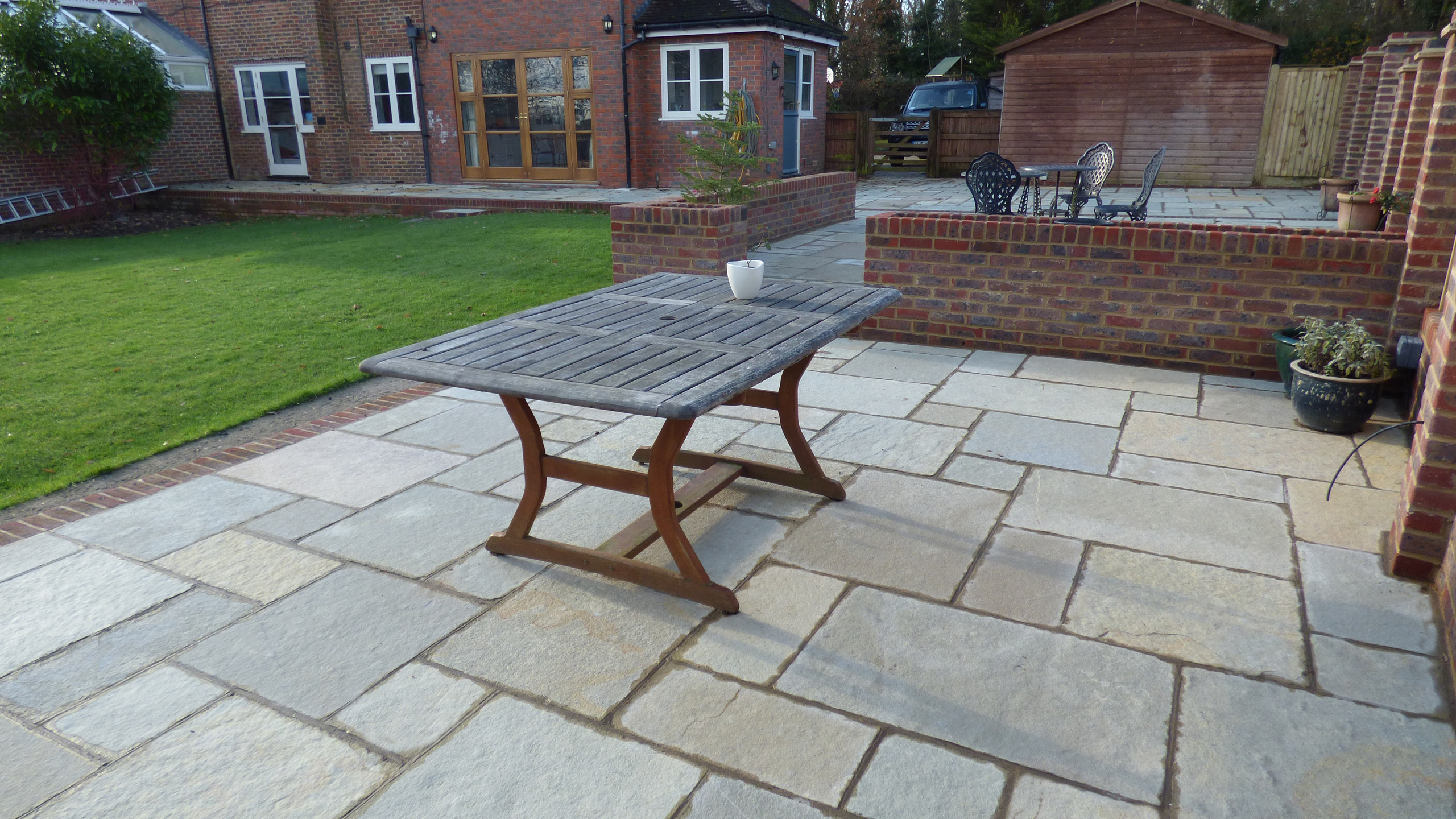 Installation of a Brett Limestone Patio with brick edging, retaining walls and flowerbeds in Sevenoaks