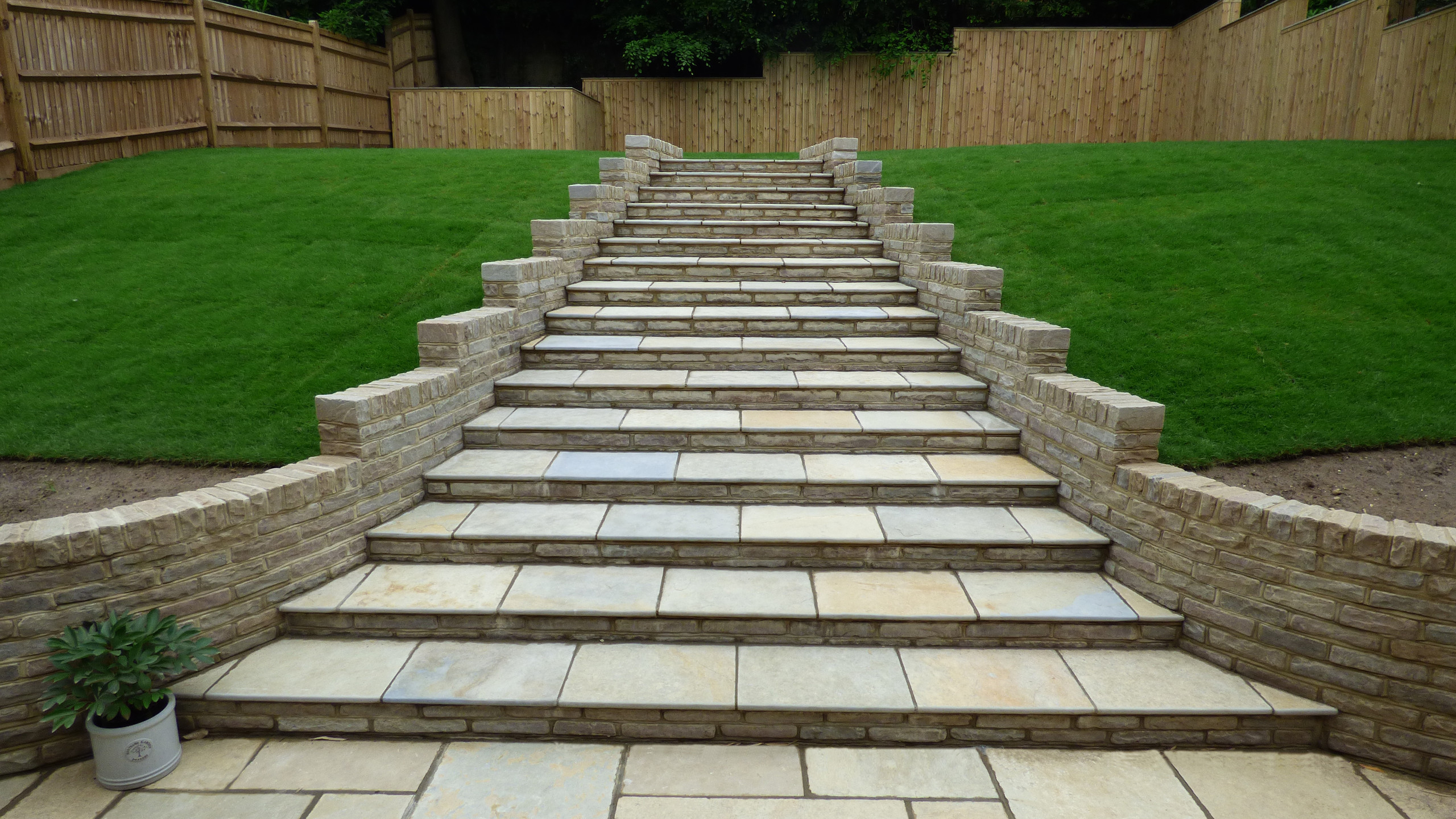 Brett Limestone patio and steps, with tumbled sandstone walling, timber clad concrete retaining walls and new lawn.