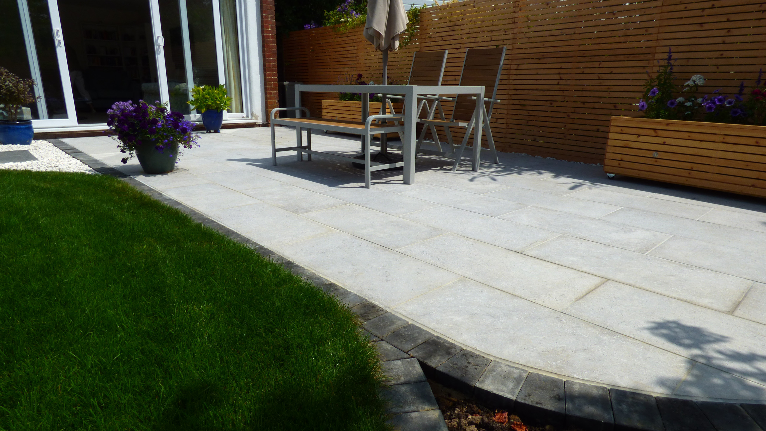 A CED Amabile porcelain patio featuring Rock Unique stepping stones, flat white pebbles and a circular lawn edged with Brett Beta Charcoal blocks.