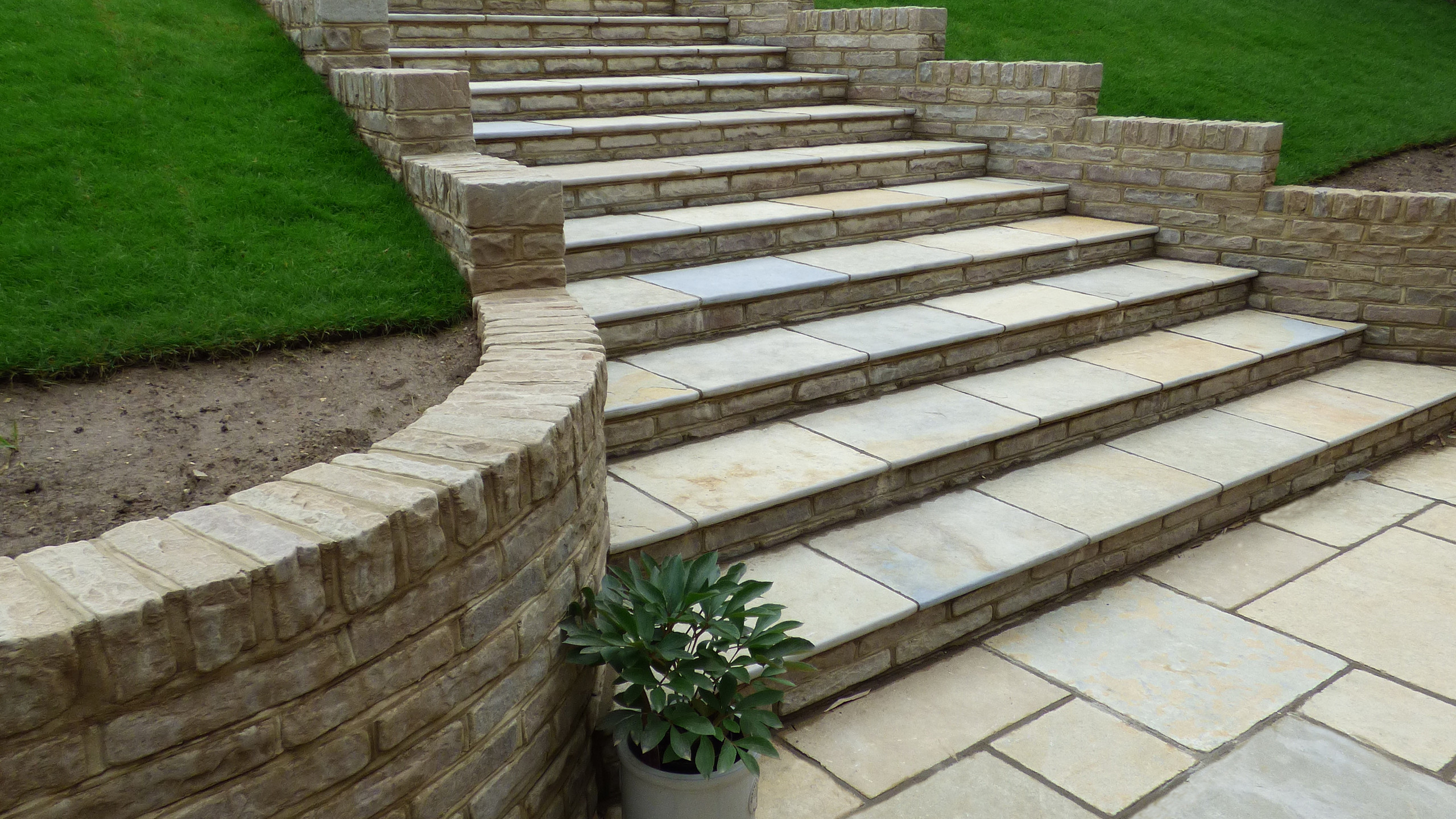 Brett Limestone patio, new lawn, steps and many retaining walls, which included tumbled sandstone walling and timber clad concrete retaining walls.