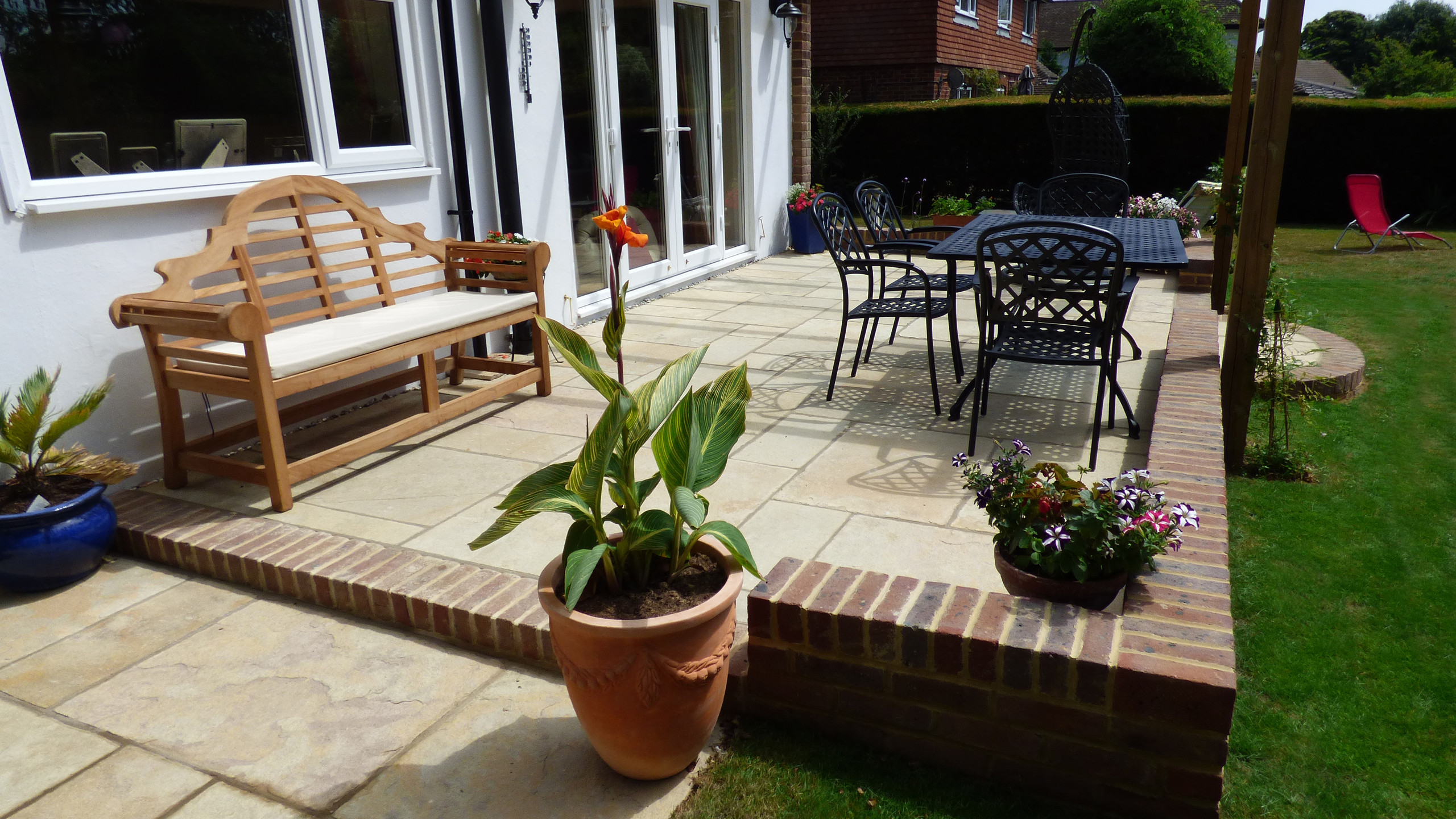 Brett Limestone patio with brick edging and retaining walls.