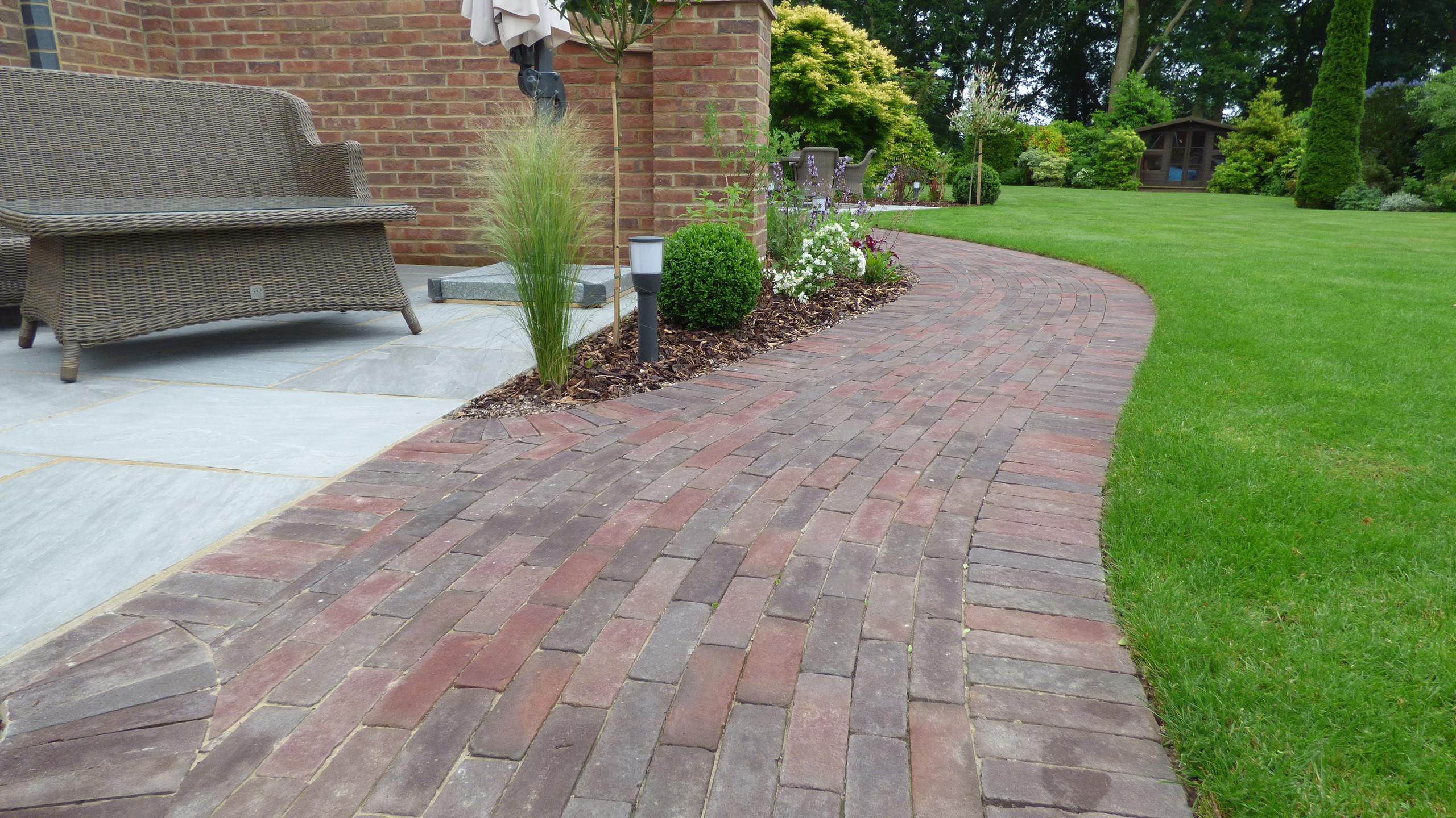 Belgium clay paving paths. And a Brett Mountain Mist Sandstone paving was used for the main patio/seating areas.