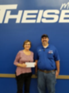 Kalen Petersen accepts a grant check from Theisen's