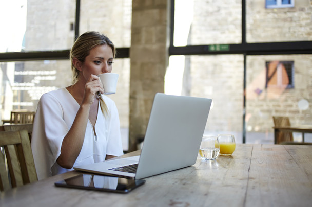 A woman working remotely on her laptop while drinking coffee