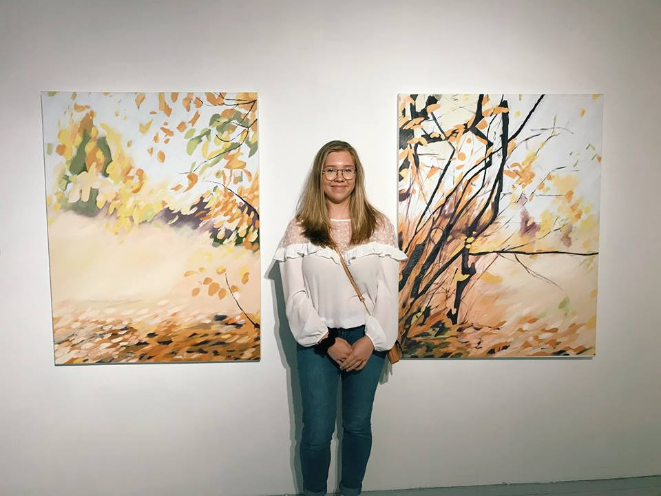 Tia Furstenberg with two of her three oil paintings on display at the Art Mûr commercial gallery