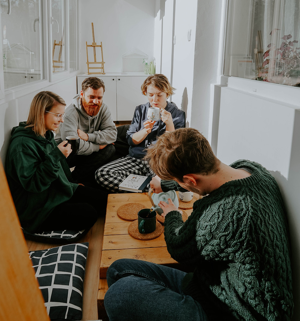 Four flatmates having coffee on a low table
