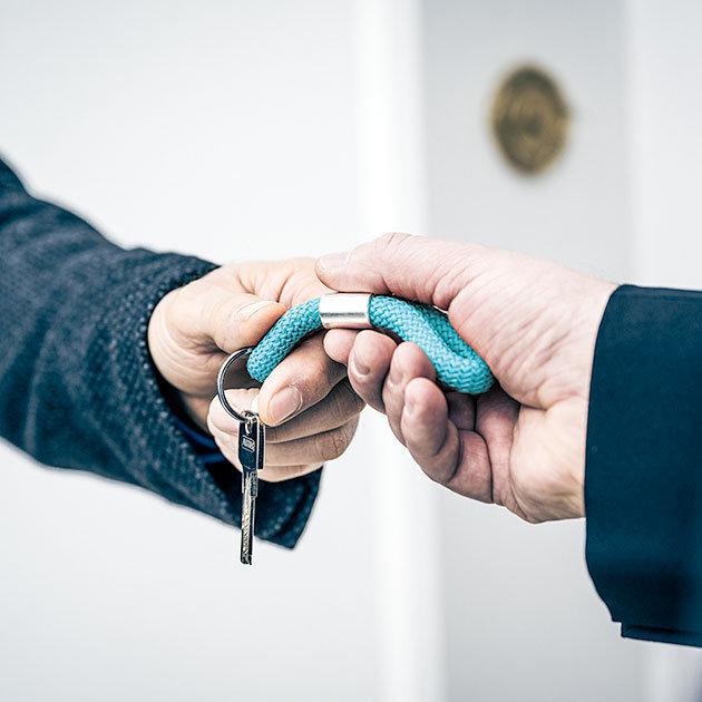 Ein Kunde übergibt Nico Lilie Immobilienverwaltung seinen Hausschlüssel