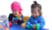 two girls are playing with colorful toys