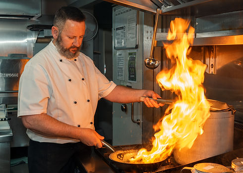 Chef Frank cooking with fire over the stove
