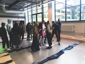 Picture of people talking at a workshop with textile on the floor