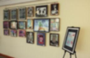 выставка детских рисунков воспитанников арт-студии Красная ворона, рисунки в черных рамках на стене, мольберт, экспозиция на стене