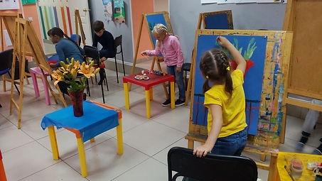 Дети рисуют пастелью на мольбертах натюрморт с оранжевыми цветами в красной вазе с натуры