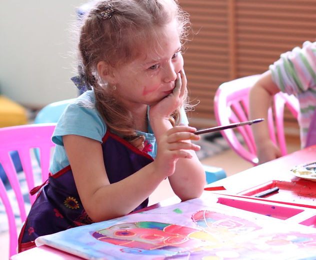 """загадочная девочка за столом с кисточкой мечтающий ребенок, занятие в студии """"Красная ворона"""", рядом работа по батику, детские занятия, обучение батику в Нижнем Тагиле, детское развитие, учимся рисовать батик, щека в красной краске, юный художник,  творческие занятия в Тагиле, запись в кружки Нижнего Тагила, уроки рисования, Нижний Тагил"""