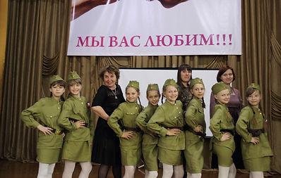 дети в камуфляжных костюмах на сцене пансионата для инвалидов и ветеранов, руководители на фоне