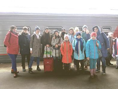 Воспитанники арт-студии Крсная ворона на перроне на фоне поезда перед поездкой в Питер