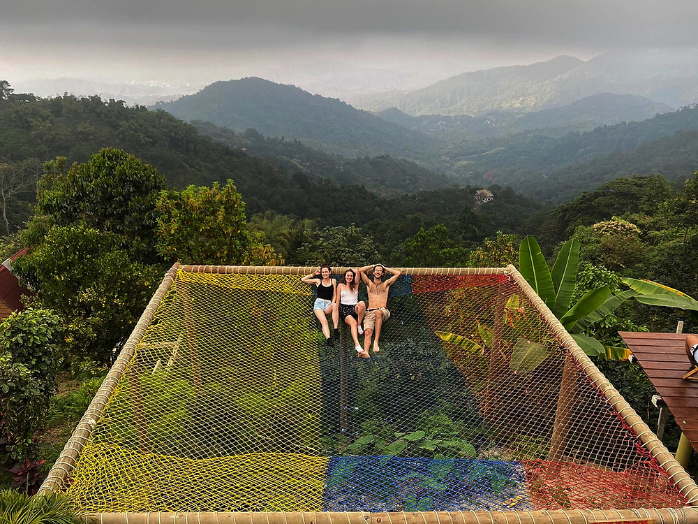Three adults on hammocks over edge of mountain in Minca, Colombia