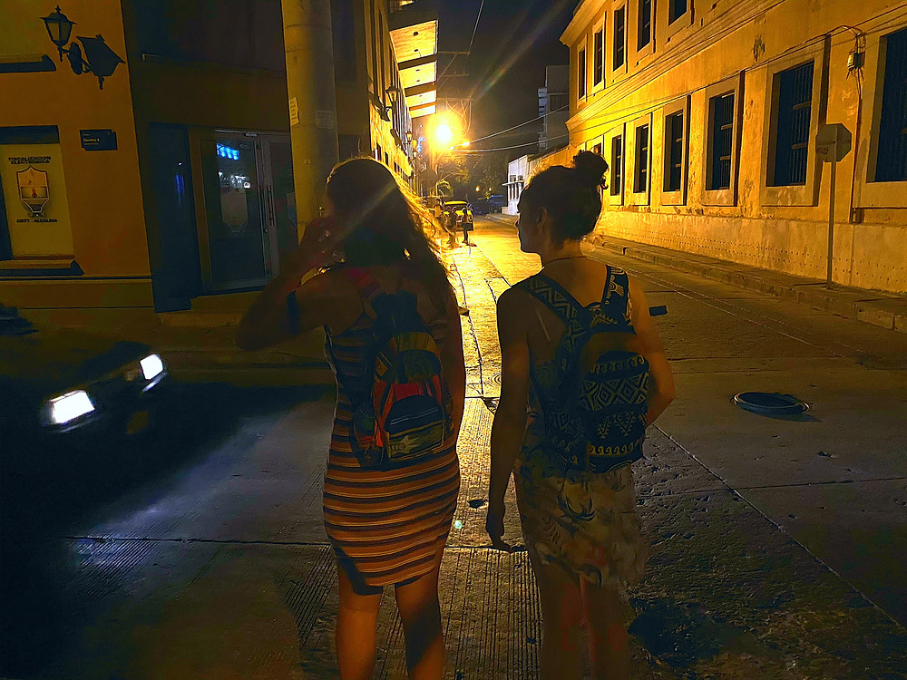 Two in dresses girls walking at night in Colombia