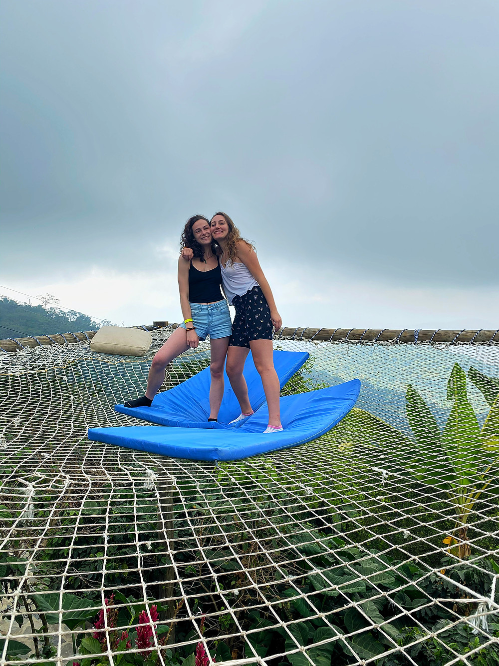 Two girls on adventure travel hammock over edge of mountain in Colombia