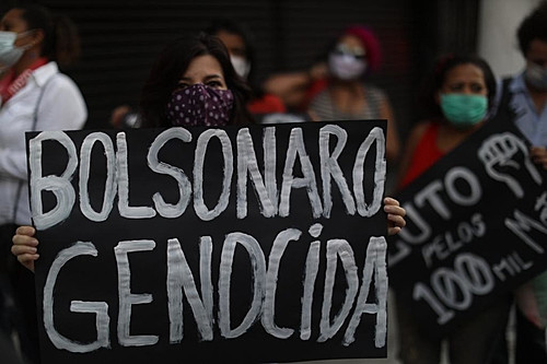 """Woman holding """"Bolsonaro Genocida"""" sign during a protest in Sao Paulo, Brazil"""