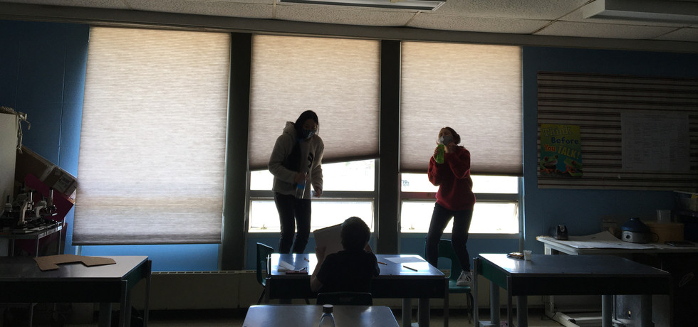 Three students singing their hearts out to k-pop during anime club.