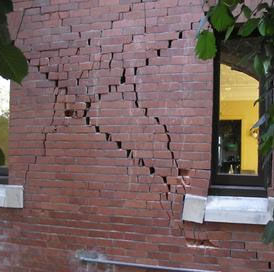 Badly cracked brick wall of building from earthquake.