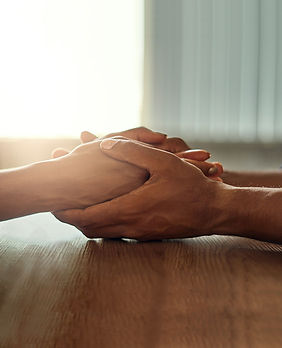 One set of hands holding another as they rest on a table top with curtained window in background.