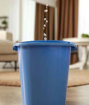 Blue plastic trashcan with water dripping into it with living room in background