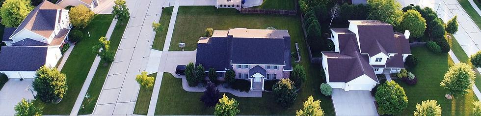 Drone view overlooking neighborhood with large homes, yards, sidewalks, & driveways.