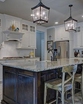 Modern kitchen, white cabinets, wooden island, granite countertops, lantern lights, stainless steel refrigerator