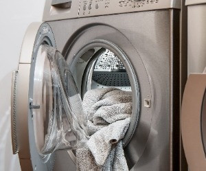 Close up of front load, stainless steel dryer with towels partially handing out of round open door.