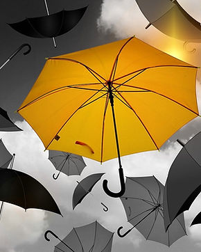 Yellow umbrella in sky surrounded by black and white umbrellas