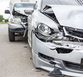 Close up of front ends of two white cars smashed in accident