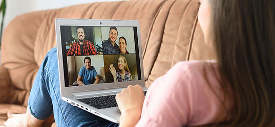 Woman sitting on sofa, facing away, looking at laptop with zoom meeting images displayed.
