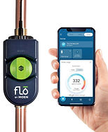 Flo by moen device connected to copper pipe, hand holding smart phone with Flo app displayed.