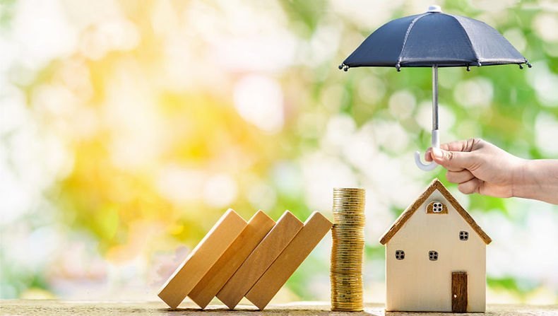 Hand holding miniature umbrella over miniature house, with stack of coins, wood blocks.