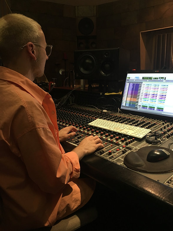 Jake Amy sitting behind Newmarket Studios recording console