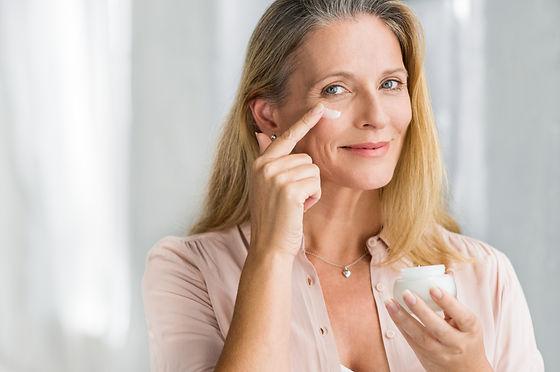 Smiling senior woman applying anti-aging