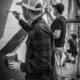 Jason Mombert assisting me in the Iver Johnson Mural, and my son, Parker watching us paint.