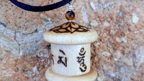 a pyrographed Mani prayer wheel pendant