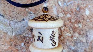 a pyrographed Mani prayer wheel pendant