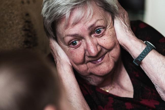 Grossmutter hält sich Ohren zu beim Spiel mit Enkel