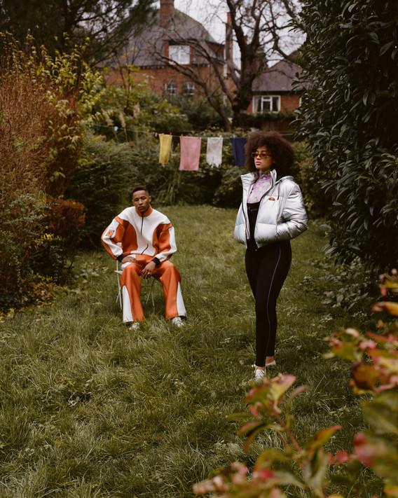 T-Allen (left): Tracksuit: Hemsley  Amandine (right): Jacket: Puffer: Ellesse  Bodysuit: Karl Kani  Top: Hildur Yeoman  Eyewear: Stylist's own