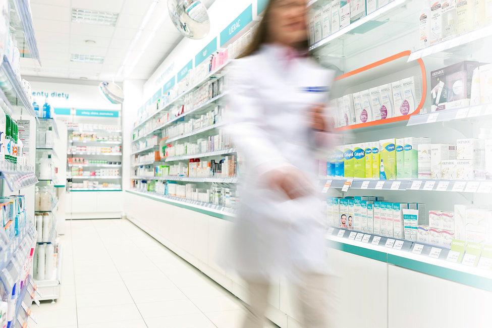 Pharmacist  in aisle of Pharmacy
