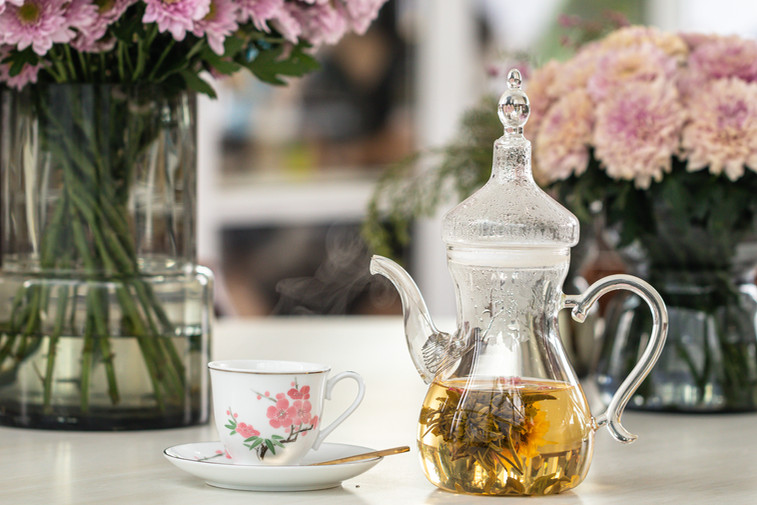 P_ and cup with blooming tea flower and