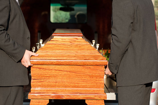 Coffin being lifted by pall bearers
