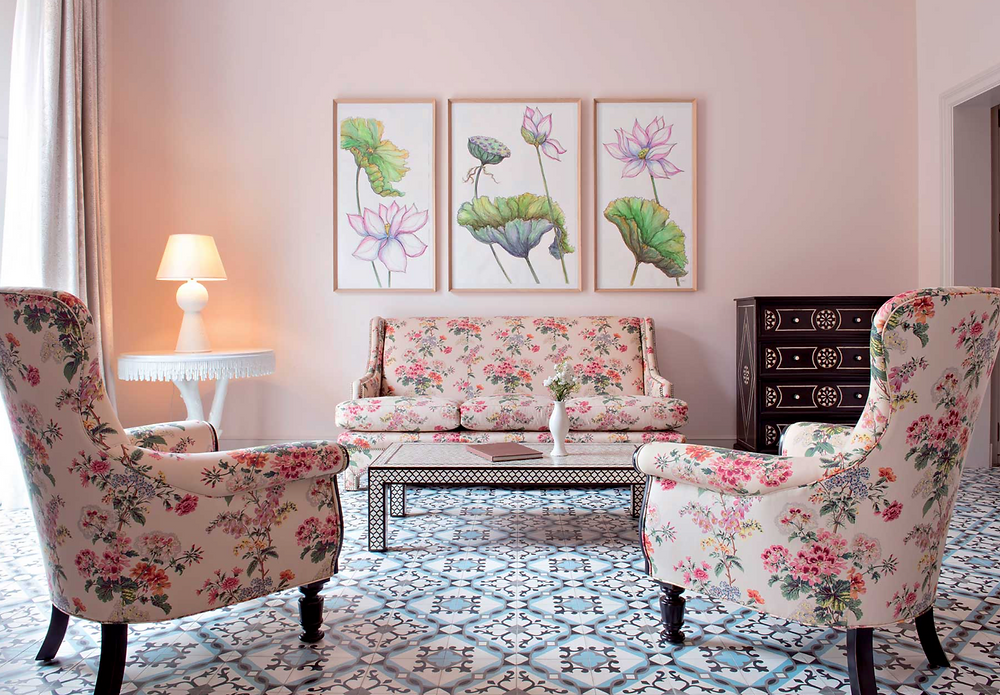 A pink bedroom with white and blue tiled floors and floral upholstery.  Botanical prints finishes off the look.