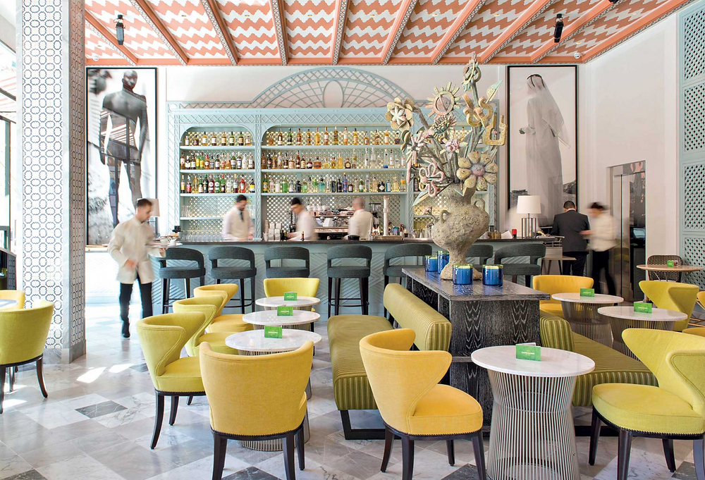 Restaurant with patterned ceiling, tiled floors and yellow chairs.