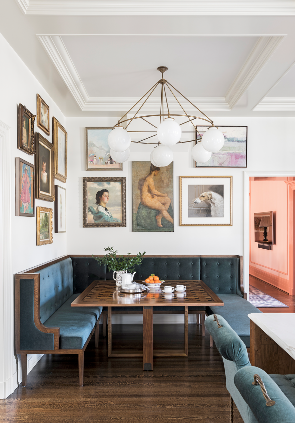 An interesting dining nook in a kitchen, with dining bench, gallery wall, beautiful chandelier and interesting ceiling.