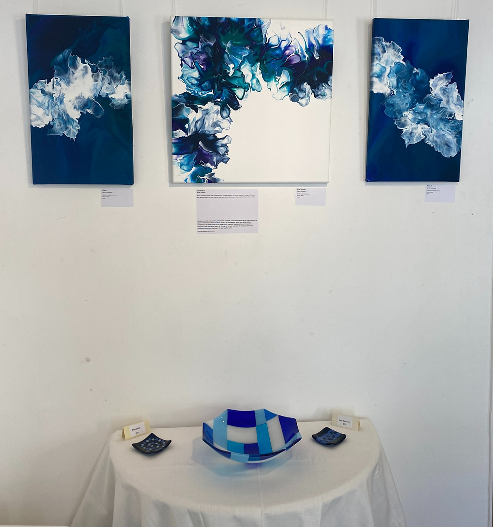 Image shows three paintings hanging on a wall: the centre painting has a white background with a wispy blue / teal / purple pattern painting across from bottom left in an arc across to top white. The two paintings on either side have a blue background with a white painted wake across it. There is a table below the paintings with a blue patterned fused glass bowl on it.
